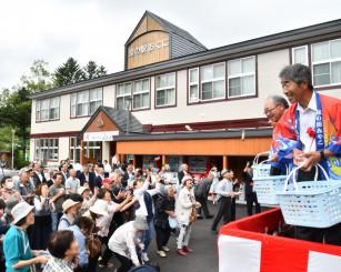 餅まきでオープンを祝う関係者や地域住民