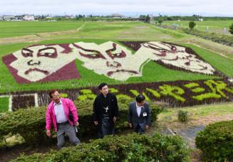 見頃を迎えた田んぼアートの鑑賞に訪れた松本幸四郎さん(中央)。アートは(左から)市川染五郎さん、松本白鸚さん、松本幸四郎さん=9日、奥州市水沢佐倉河