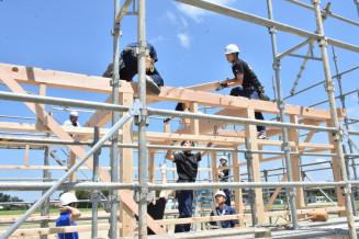 整備中の公園にあずまやを建築する学生たち