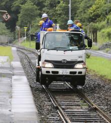 JR釜石線で動物と列車の接触事故を防ぐため、液剤を散布する作業員=12日午後、釜石市