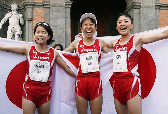 女子ハーフマラソンで優勝し、日の丸を掲げる鈴木優花(中央)。左は2位の加世田梨花、右は3位の田川友貴=ナポリ(共同)