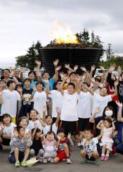 1964年東京五輪の聖火台の点火イベントで手を振る参加者ら=14日午後、陸前高田市