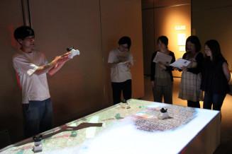 展示会関係者に作品を説明する企画担当者(左)