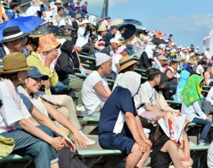 強い日差しの中、タオルや帽子をかぶって試合を見守る観客=20日、花巻市・花巻球場