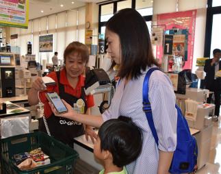 「コープペイ」アプリでスマホ決済する買い物客