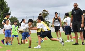 ラグビーの日本代表選手からステップを教わる児童ら=23日、盛岡市永井