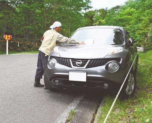 県道から逸脱して駐車する車を注意する文書を貼る早池峰国定公園自然公園保護管理員(画像の一部を加工しています)=遠野市・小田越登山口付近