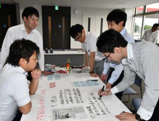 持ち寄った記事の切り抜きを基に、地域貢献策について、班ごとに意見をまとめる若手社員