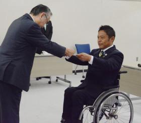 八木橋伸之委員長から当選証書を受け取る横沢高徳氏(右)