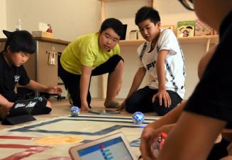 タブレット端末を使って球状のロボットを動かす子どもたち