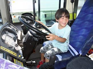 楽しそうにバスの運転席に座る子ども