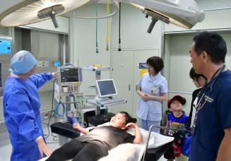 手術室のベッドで脈拍などを測定してもらう来場者