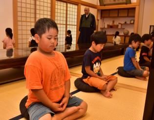 暑さの中、背筋を伸ばし座禅を体験する子どもたち