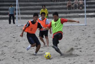 砂浜で懸命にボールを追いかける参加者