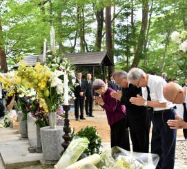 慰霊碑の前で手を合わせ、犠牲者を追悼する参列者