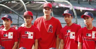 試合前、球場を訪れた宮城、熊本両県の中学生と記念撮影するエンゼルス・大谷翔平(中央)=アナハイム(共同)