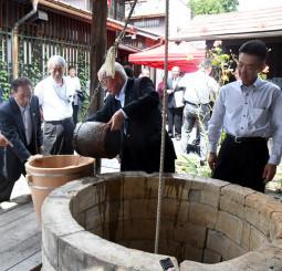 井戸から水をくみ上げ、ひとときの涼を感じる出席者