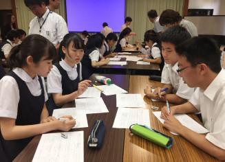 新聞で調べた企業動向のグループ発表を評価し合う宇都宮商高の生徒