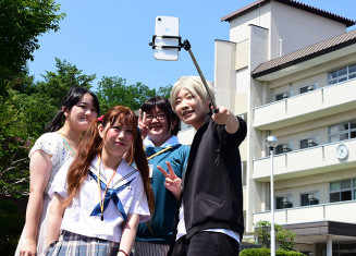 ファンの「聖地」の一つとされる軽米高を背に写真撮影する参加者
