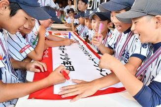 横断幕に全国大会への意気込みを書き込む千徳小スポ少の選手