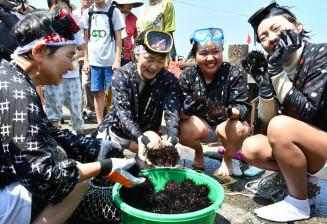 素潜りで採ったウニを披露する大道琉伽さん(右から2人目)ら