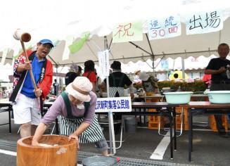 勢いよく餅をつく30回連続出場の金沢新町集落公民館のメンバー