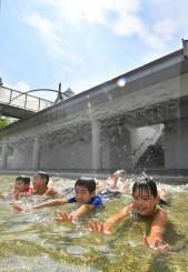 強い日差しの中で水遊びを楽しむ子どもたち=5日、一戸町奥中山・いわて子どもの森