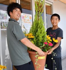 いのちをつなぐ未来館の佐々学さんに鉢を手渡す大越逸平君(右)