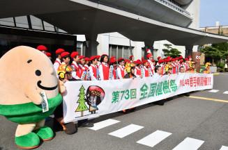 演奏を披露した寄木小鼓笛隊の児童らと全国植樹祭の本県開催を伝える横断幕=7日、盛岡市内丸・県庁