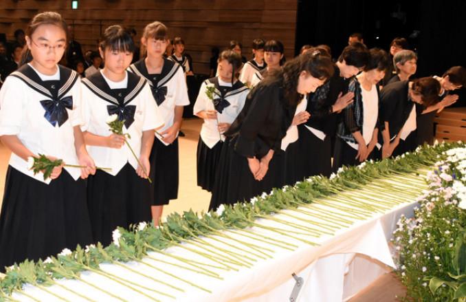献花台に花を手向け、犠牲者の冥福を祈る参列者ら