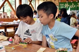 木工工作体験を通して玉山地域の児童と交流を深める渡辺宥心君(右)