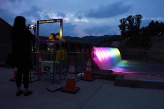 ライトアップされた貯砂ダムの前で記念撮影する家族ら