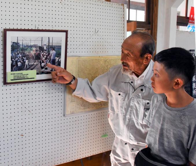 来場者に写真を説明する菅原唯夫さん(左)