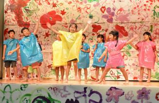 描いた絵の前で歌ったり踊ったりする子どもたち