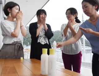 「甘糀化粧水」を手に取り、香りなどを確かめる参加者