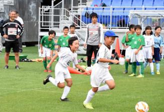 元女子日本代表監督の佐々木則夫さん(左)が見守る中で練習する子どもたち