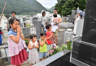 祖先の墓を訪れ、手を合わせる家族=13日、岩泉町岩泉・雲岩寺