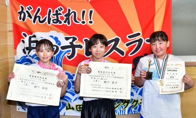 賞状とメダルを掲げ、さらなる高みを目指す(右から)舘下苺采さん、舘下莉子さん、舘下姫朋さん