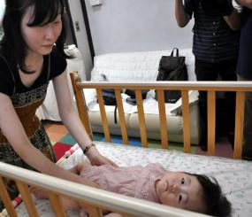 ベビーベッドやソファを設置した赤ちゃんの駅で長女小百合ちゃんをあやす及川梢さん(左)