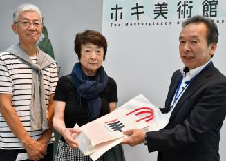 藁谷収館長(右)から入場1万人目の記念品を受け取る船越和幸さん、素子さん夫妻