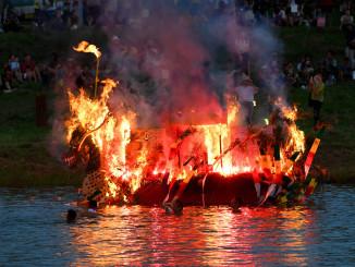 川面を赤く染める激しい炎を上げながら川を流れる舟=17日午後6時34分、盛岡市・明治橋上流