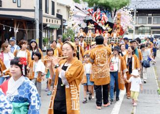 笛や太鼓の音色を響かせて、JR荒屋新町駅前を練り歩く参加者