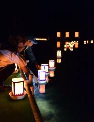 祈りを込めた灯籠を大泉が池に浮かべる人たち