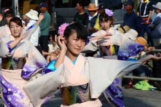 流し踊りで息の合った手さばきを見せる参加者。華やかな踊りが通りを彩った