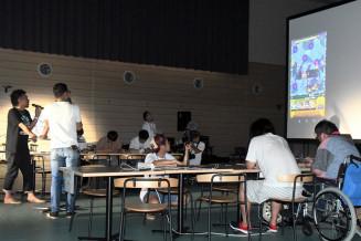 大型スクリーンにゲーム画面が映し出され、手元の端末で対戦する参加者