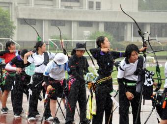 雨の中、集中して矢を放つ全国の高校生=20日、雫石町・雫石総合運動公園