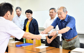 中務秀雄総合政策部長に要望書を手渡す八屋勉会長(右)