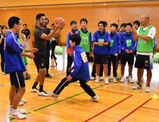 ボールを使ったゲームで生徒と交流する伊藤剛臣さん(右)