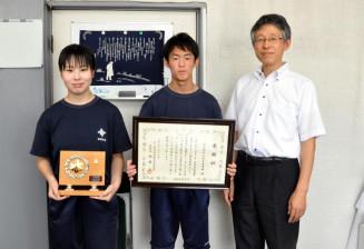 迅速な連携による人命救助に贈られた感謝状を掲げる(左から)松岡那奈さん、田原成隆さん、柿崎肇校長