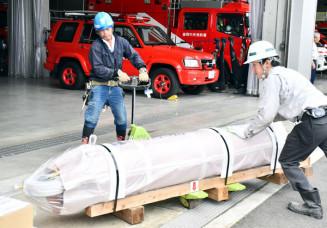 新品のオイルダンパーを盛岡中央消防署庁舎の地下へ運び込む作業員